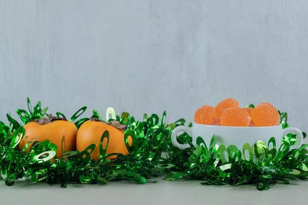 Paire de kakis frais aux marmelades d'oranges.