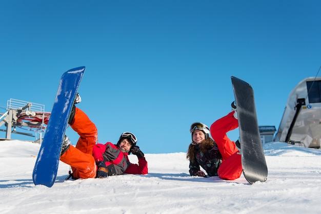 Paire avec leurs snowboards allongés dans la neige sur une piste de ski