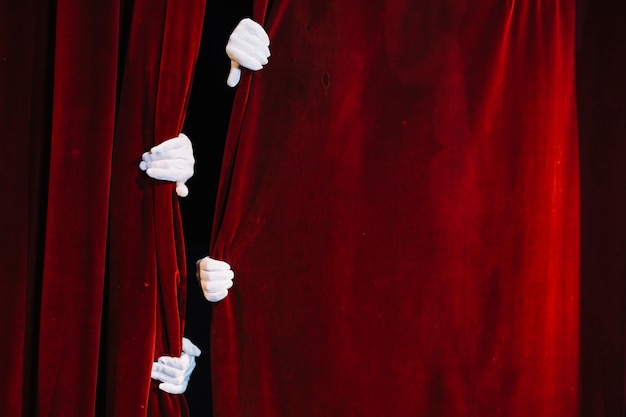 Paire de main de mime tenant un rideau rouge fermé