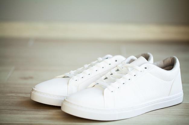 Paire de nouvelles baskets blanches élégantes au sol à la maison