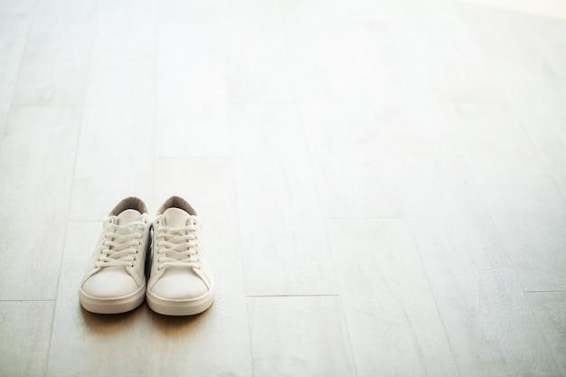 Paire de nouvelles baskets blanches élégantes sur un plancher en bois.