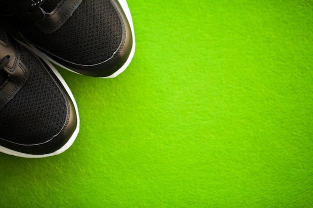 Paire de nouvelles baskets élégantes sur fond vert.