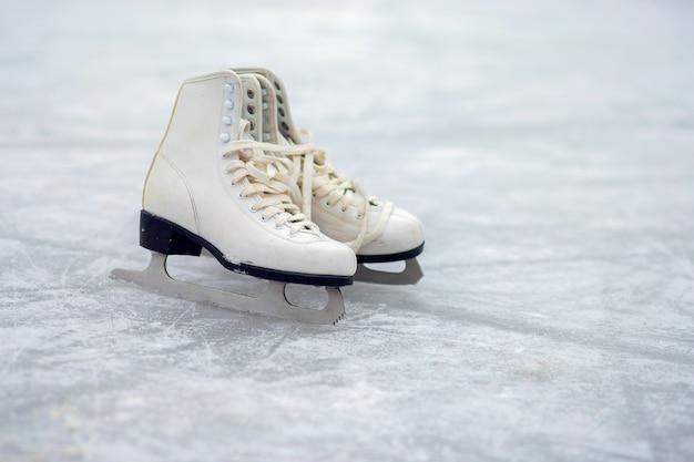 Une paire de patins à glace blancs se tient sur une patinoire ouverte. sport d'hiver
