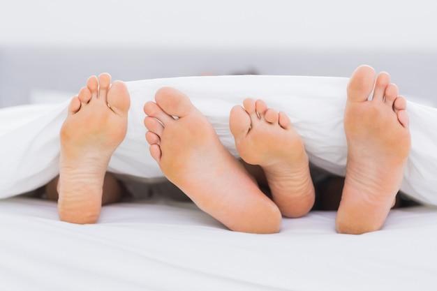Paire de pieds sous les couvertures