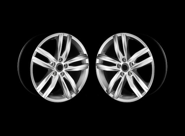 Paire de roues de voiture en aluminium modernes dans une lumière dramatique. photo en miroir. isolé.