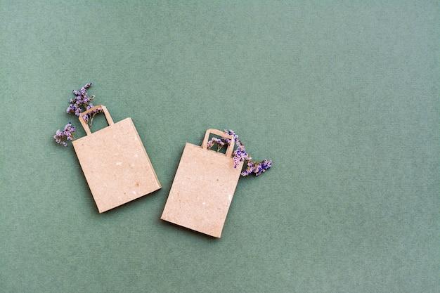 Paire de sacs à provisions en papier kraft écologique avec des fleurs séchées sur fond vert. ventes de cadeaux du vendredi noir. espace de copie