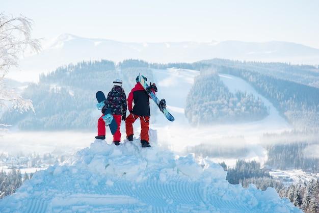Paire de snowboarders au sommet d'une montagne