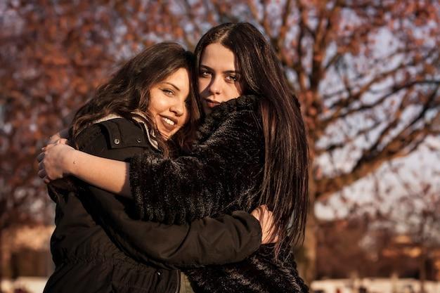 Paire de sœurs s'embrassant avec amour dans un parc en plein air, symbole de l'amour fraternel
