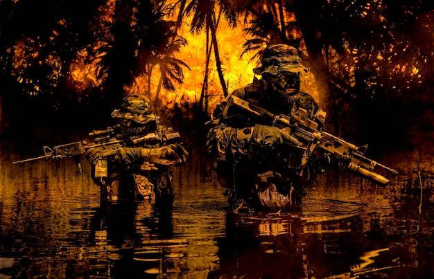 Paire de soldats en action lors d'un raid fluvial dans la jungle jusqu'à la taille dans l'eau et la boue et se couvrant les uns les autres