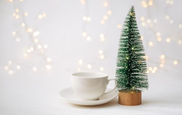Une paire de thé et un petit arbre de noël artificiel sur fond blanc avec un bokeh avec une place pour le texte