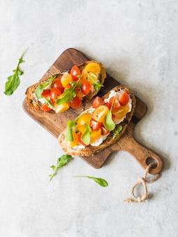 Paire de toasts grillés avec du fromage à la crème et des tranches de tomates fraîches de différentes couleurs avec de la roquette fraîche et du poivre noir moulu