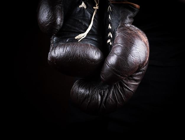 Paire de très vieux gants de boxe marron suspendus