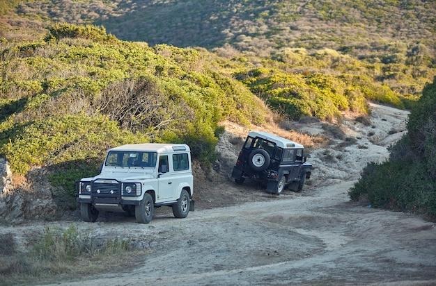 Paire de véhicules tout-terrain sur un chemin de terre garé symbole d'excursion dans la désolation