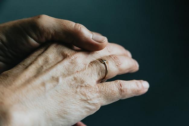 Une paire de vieilles mains montrant une bague de bijoux sur le doigt sur un fond sombre