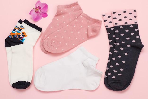 Paires de couleurs de chaussettes pour femmes et fleur d'orchidée sur fond coloré, vue de dessus.