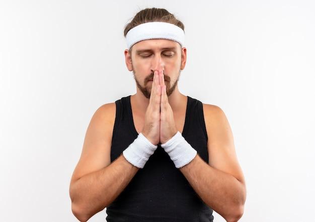 Paisible jeune bel homme sportif portant bandeau et bracelets mettant les mains ensemble dans le geste de prier avec les yeux fermés isolé sur un espace blanc