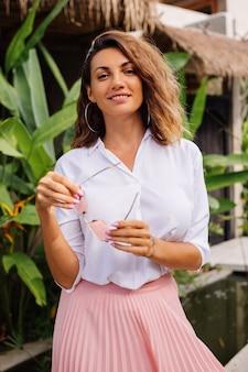 Paisible jeune femme heureuse avec de courts cheveux bouclés en jupe longue rose et chemise blanche seule à l'extérieur de sa villa