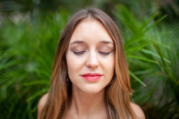 Paisible jeune femme avec des yeux fermés, appréciant les sons de la nature