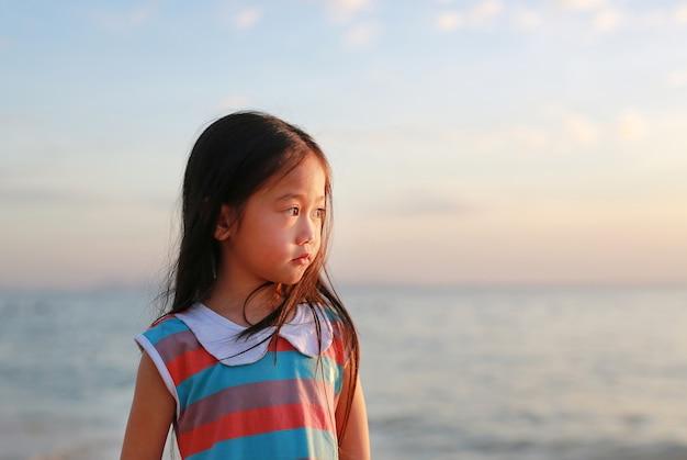 Paisible petite fille enfant debout sur la plage à la lumière du coucher du soleil avec regarder.