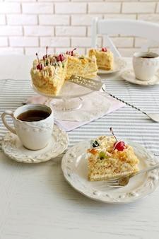 Paix de délicieux gâteau au beurre sur plaque, tasses à thé sur fond en bois de couleur