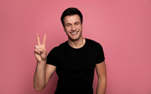 Paix pour tous. jeune homme charismatique dans un t-shirt noir, qui regarde la caméra avec un grand sourire et montrant un signe de paix.