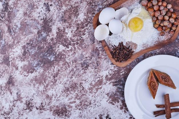 Pakhlava du caucase avec des bâtons de cannelle dans une assiette blanche avec planche d'ingrédients de côté