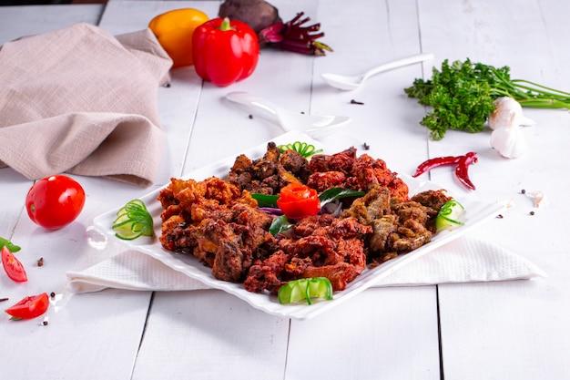 Pakoda au poulet ou pakoratrois saveurs différentes de pakora disposées dans une assiette carrée blanche