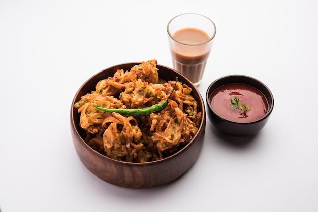 Pakora aux oignons frits ou pyaj pakoda également connu sous le nom de crispy kanda bhaji /bhajji / bajji, collation indienne préférée à l'heure du thé pendant la saison des pluies. servi avec du ketchup aux tomates