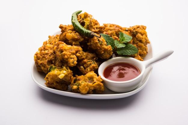 Pakora ou pakoda de maïs croustillant, bhajji, bhaji, bajji ou pattice. servi avec du ketchup aux tomates
