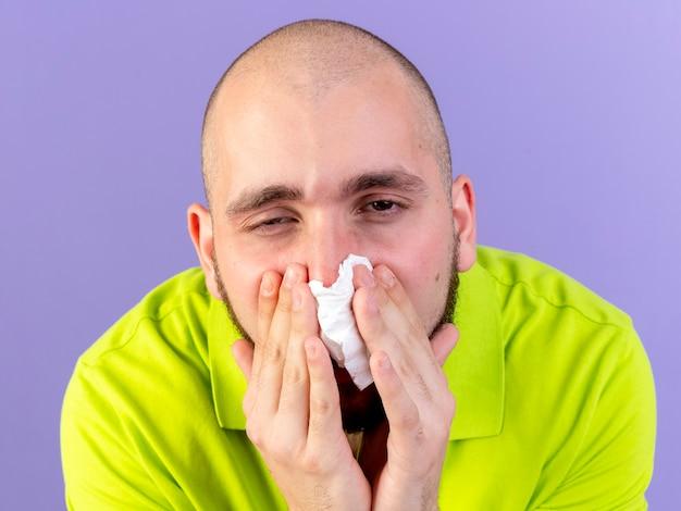 Pâle jeune homme malade de race blanche essuie le nez avec du tissu isolé sur un mur violet avec copie espace