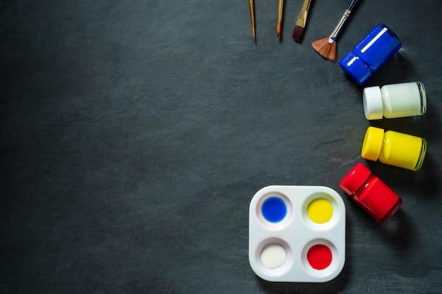 Palette et aquarelle avec un pinceau sur fond de ciment noir