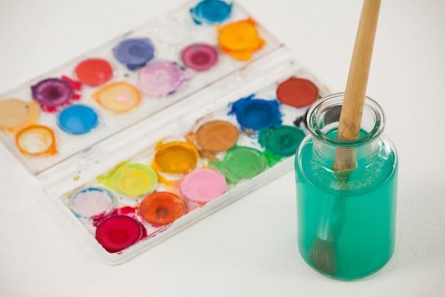 Palette d'aquarelle et pinceau avec de la peinture bleue trempée dans l'eau contre une surface blanche