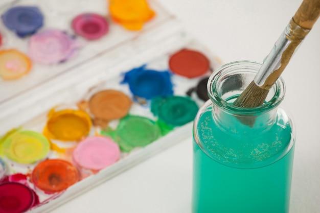 Palette d'aquarelle et pinceau avec de la peinture bleue trempée dans l'eau sur fond blanc