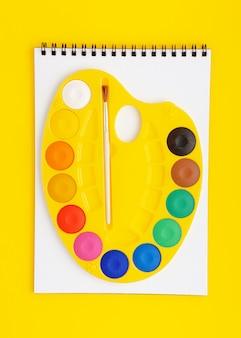 Palette aquarelle sur scetchbook sur fond jaune. concept de dessin.