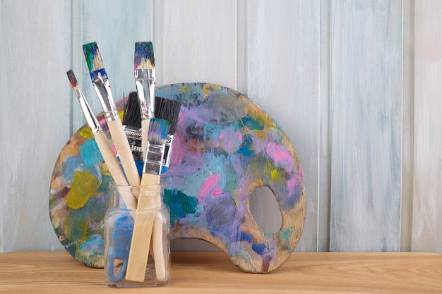 Palette d'art en bois avec peintures et pinceaux