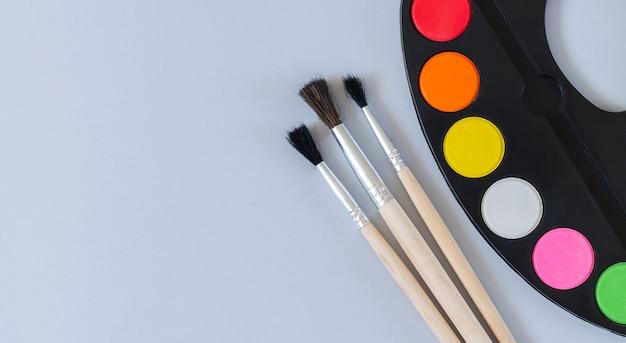 Palette d'art avec peinture et pinceaux vue de dessus sur une surface grise, bannière avec espace de copie