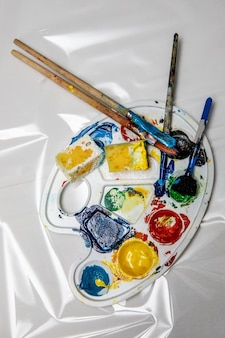 Palette d'art avec des tubes de peintures à l'aquarelle et des pinceaux.