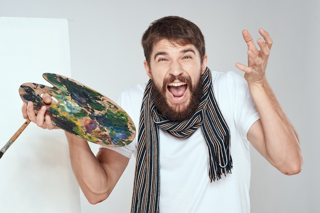 La palette de l'artiste et dans les mains d'une écharpe hobby art chevalet autour du cou un fond clair. photo de haute qualité