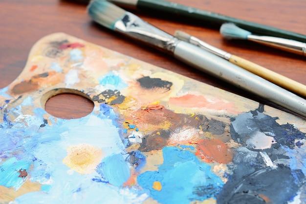 Palette de l'artiste avec des traits de peinture à l'huile colorés et des pinceaux