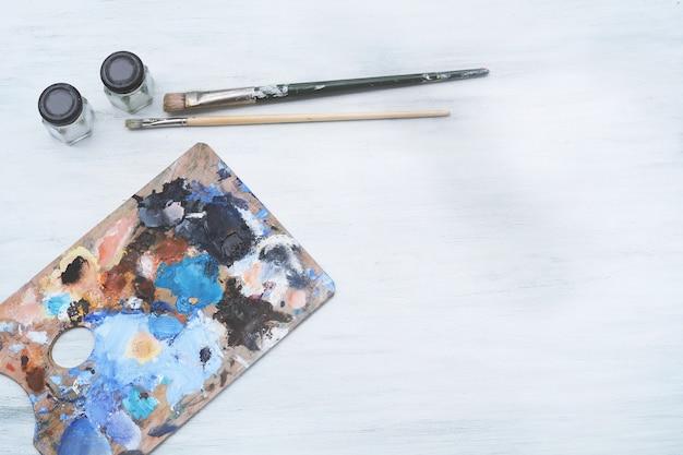 Palette d'artiste avec des traits de peinture à l'huile colorés et des pinceaux