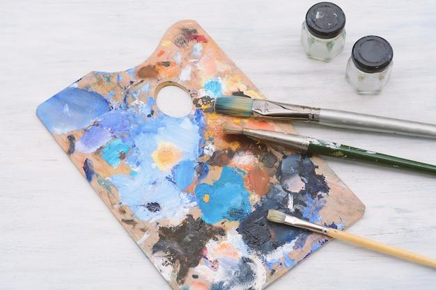 Palette de l'artiste avec des traits de peinture à l'huile colorés, des pots et des pinceaux