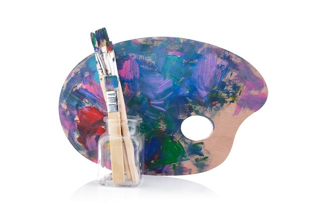Palette en bois avec peintures et pinceaux
