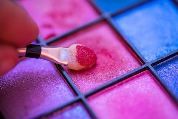 Palette colorée pour le maquillage avec la main tenant le pinceau