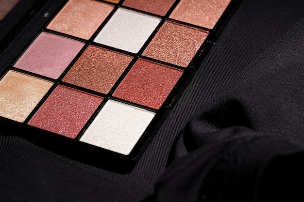 Palette cosmétique professionnelle de couleur sur fond sombre, gros plan