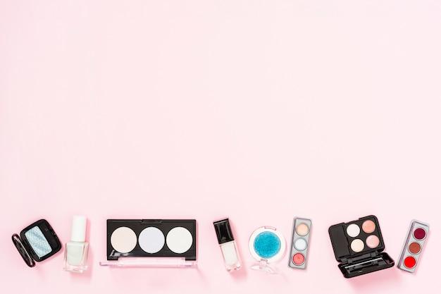 Palette de cosmétiques avec des bouteilles de vernis à ongles sur fond rose