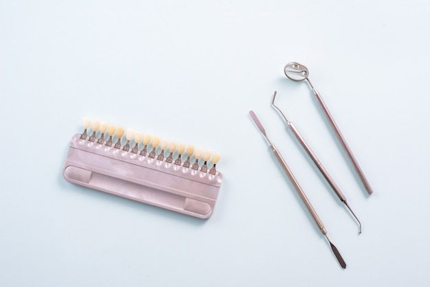 Palette de couleurs de différentes nuances de dents et d'outils dentaires sur fond bleu. concept de blanchiment des dents