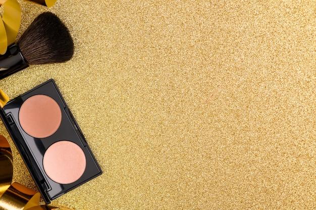 Palette de fondation sur un fond festif brillant avec des paillettes, à plat. accessoire cosmétique de beauté pour femme pour un teint parfait. poudre beige avec brosse et vue de dessus de confettis. espace de copie.