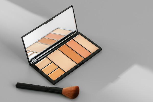 Palette de maquillage avec des correcteurs colorés sur fond gris