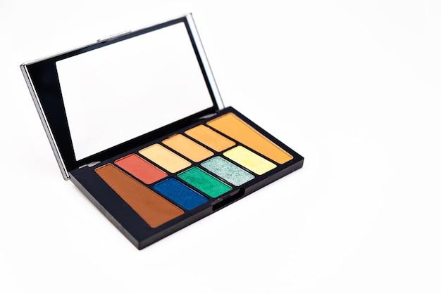 Palette de maquillage de fard à paupières coloré isolé sur une surface blanche composent des outils d'artiste