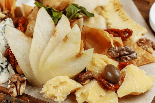 Palette de nombreux types de fromages et quelques raisins, olives.